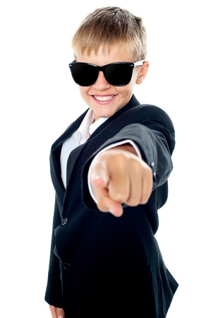 kid pointing: Cheerful young kid pointing towards the camera. Dressed like a businessman