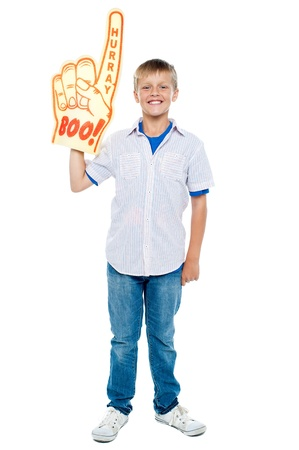hurray: Full length portrait of a stylish young boy wearing a large foam hand. Boo and hurray!