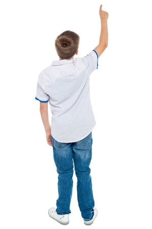 standing alone: Rear view of a school boy over white background pointing upwards. Full length portrait Stock Photo