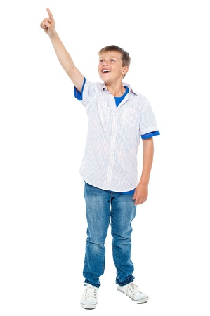 casuals: Charming young boy pointing towards copyspace area. Dressed in casuals