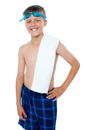 Happy 13 years old boy with goggles and towel. All against white background photo
