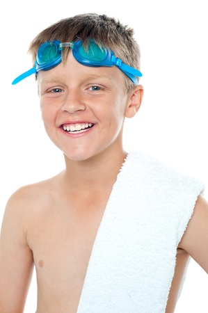 Closeup of champion swimmer boy wearing goggles on head along with towel on his shoulder photo
