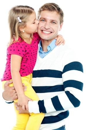 pere et fille: Douce fille embrassant son p�re en souriant pendant qu'il la tient dans ses bras