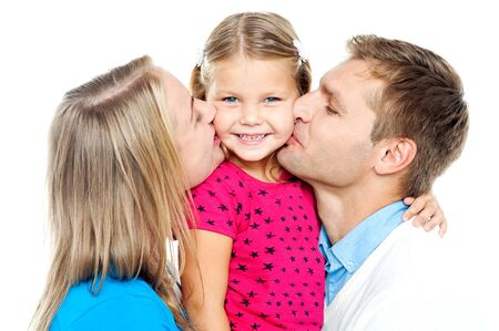 Mom and dad kissing their beautiful kid on cheeks from both the sides photo