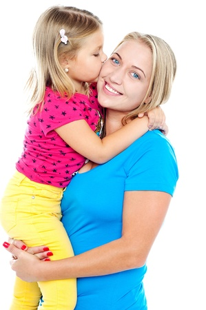 Fashionable young kid kissing her mother while mum holds her up photo