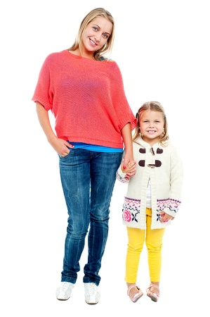 Mum and daughter posing in trendy outfits. Full length portrait photo