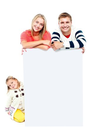 Couple standing behind blank white ad board while their daughter sitting on the floor photo