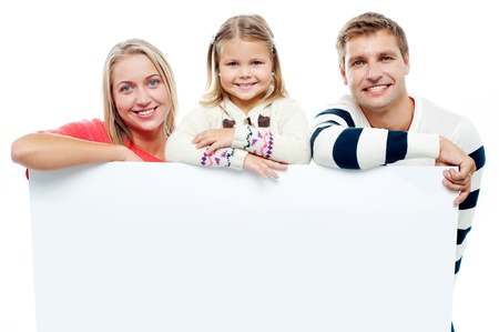 Smiling family with whiteboard in a studio looking at camera photo