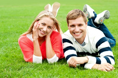 Happy young couple outdoors. Lying on lush green grass photo