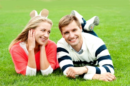 Romantic young couple outdoors in the park. Lying and relaxing photo