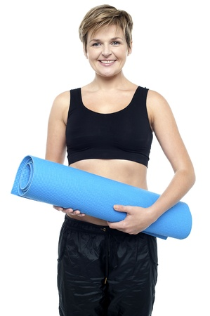 Profile shot of a health conscious woman in workout clothes holding blue exercise mat Stock Photo - 16167234