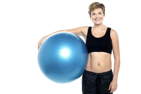 An attractive fit lady holding blue pilates ball isolated against white background Stock Photo - 16167268