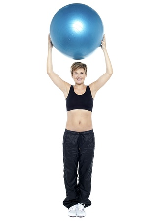 Glamorous woman doing pilates exercise. Lifting ball above her head Stock Photo - 16167210