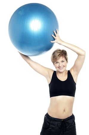 A healthy woman lifting big swiss ball isolated on white Stock Photo - 16167270