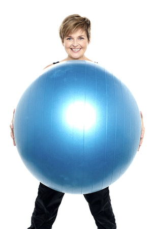 Charming woman holding big blue fitness ball in front of camera Stock Photo - 16167217