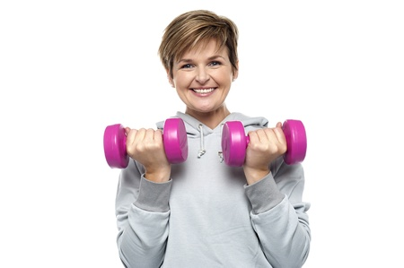 Beautiful young woman with dumbbells isolated against white background photo