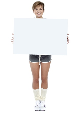 Pretty woman presenting blank whiteboard. Full length portrait photo