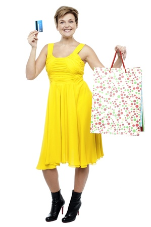 Stylish woman holding shopping bags and flashing her credit card Stock Photo - 16167276