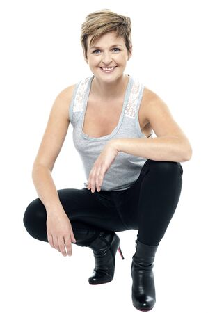 Charming woman in squatting posture, wearing boots. Studio shot photo