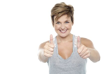 Excited middle aged lady standing in front of camera and showing double thumbs up sign Stock Photo - 16167254