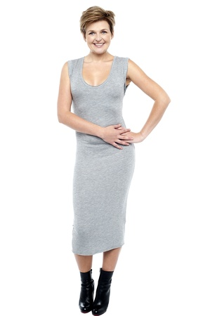 Glamorous charming woman in long grey dress on white background photo