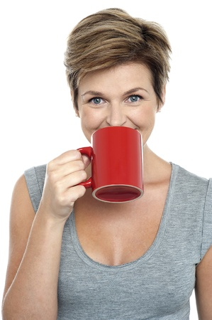 Beautiful woman drinking coffee in bright red mug. Studio shot photo