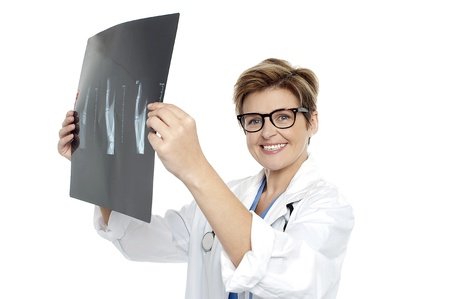 Experienced female doctor examining x-ray report. All on white background photo