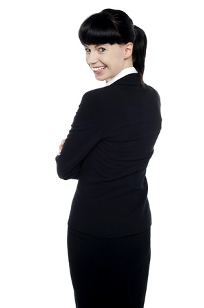 Young corporate lady turning back and smiling while looking at the camera photo