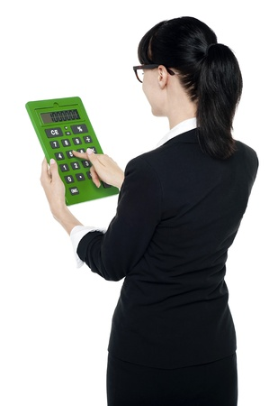 Rear view of corporate woman using big green calculator, pressing key 5 photo