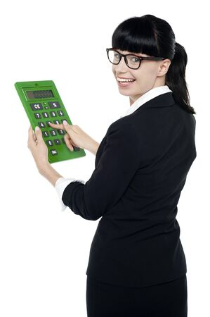 Bespectacled woman turning back, holding calculator. Isolated on white photo