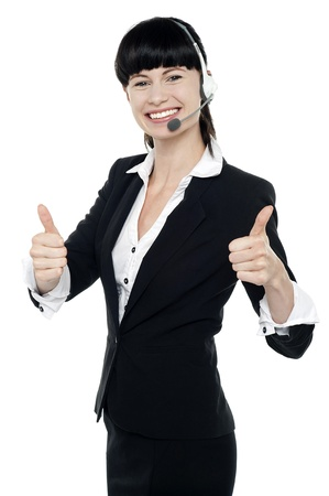 Gorgeous female telecaller with headsets on showing double thumbs up to the camera Stock Photo - 16405327
