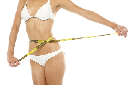 Cropped image of a fit woman with an iron board abs, measuring her waist photo
