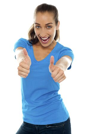 Overjoyed woman standing against white background and showing double thumbs up. Stock Photo - 16469226
