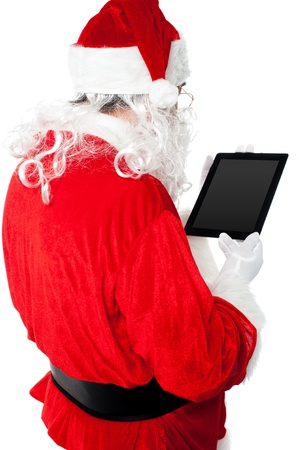 Back view of Santa looking at tablet device screen. All on white background photo