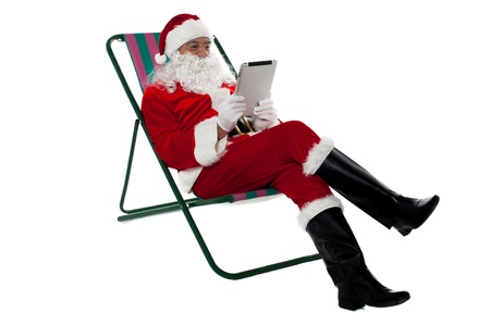 kris kringle: Kris Kringle relaxing on chair and using electronic tablet. Isolated on white.
