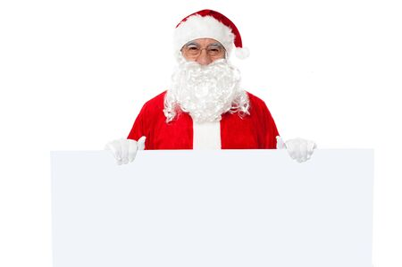 Joyful Santa standing behind a blank ad board. Advertise your business. Stock Photo - 16510028