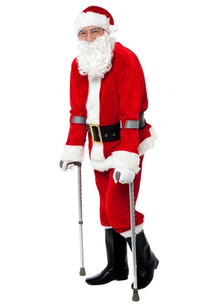 physically: Physically disabled Santa walking with the help of crutches. Stock Photo