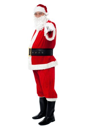 Senior man in Santa costume pointing at you. Isolated against white background. Stock Photo - 16510097