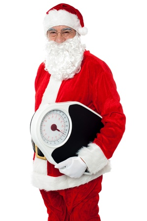 Aged male Santa holding weighing scale machine. Health concept photo