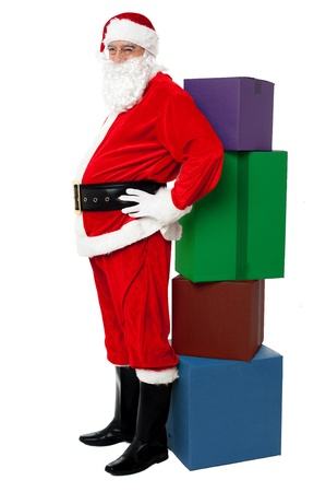 kris kringle: Christmas Theme. Happy Santa Claus leaning over colorful pile of Xmas presents Stock Photo