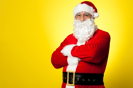 saint nick: Saint Nick posing confidently against yellow background, arms folded. Stock Photo