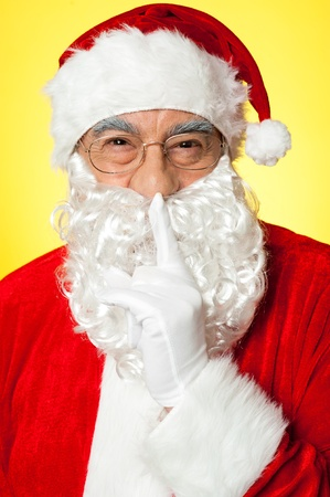 Shh...Aged Santa gesturing silence. Closeup over yellow background. photo