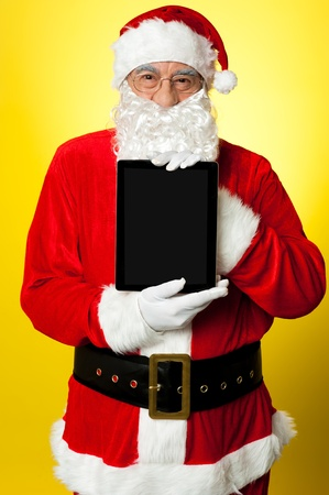 Kris Kringle presenting new updated tablet pc. Its for sale this Christmas. Stock Photo - 16510947
