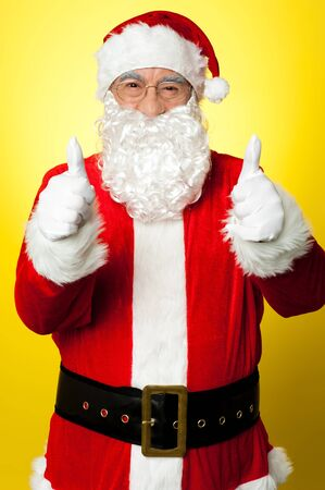 Cheerful male in Santa costume showing double thumbs up. Christmas concept. Stock Photo - 16511036
