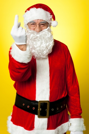 Angry Santa showing middle finger. Isolated on yellow background. photo