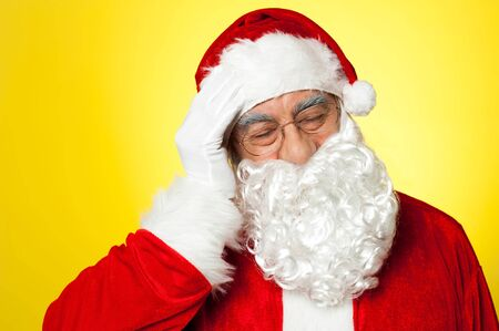 Portrait of Santa Claus suffering from headache. All on yellow background Stock Photo - 16510991