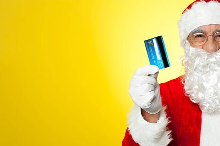Its shopping time. Cropped image of aged Santa holding credit card. photo