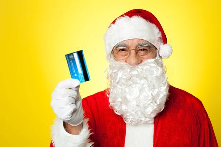 Aged man in Santa clothing ready to shop this Christmas, holding debit card. photo