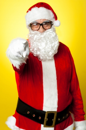 Jelly-belly Santa in spectacles pointing at you. Isolated on yellow. Stock Photo - 16510402