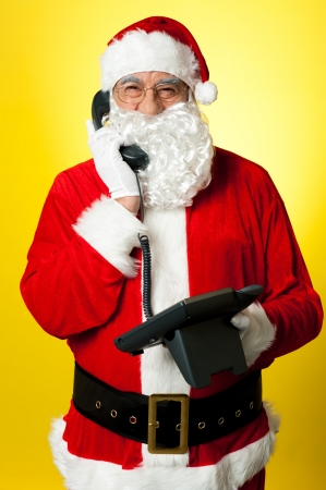 Smiling aged Santa attending phone call isolated against yellow background. Stock Photo - 16511017